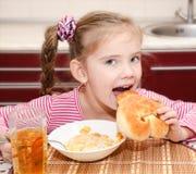 Śliczna uśmiechnięta mała dziewczynka ma śniadaniowych zboża Obraz Stock