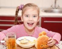 Śliczna uśmiechnięta mała dziewczynka ma śniadaniowych zboża z mlekiem Zdjęcie Royalty Free