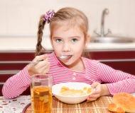 Śliczna uśmiechnięta mała dziewczynka ma śniadaniowych zboża z mlekiem Obrazy Stock