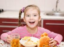 Śliczna uśmiechnięta mała dziewczynka ma śniadaniowych zboża z mlekiem Zdjęcia Stock