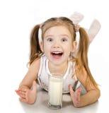 Śliczna uśmiechnięta mała dziewczynka pije mleko odizolowywającego zdjęcia stock