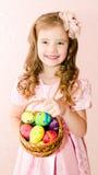 Śliczna uśmiechnięta mała dziewczynka z koszykowy pełnym kolorowy Easter jajko Fotografia Stock