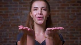 Śliczna urocza caucasian imbirowa kobieta wysyła wiatrowych sikkes i demonstruje przy kamerą jej szczęśliwego nastroju i miłości