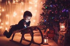 Śliczna urocza chłopiec czyta książkę przed choinką Obraz Stock