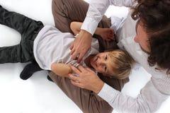 Śliczna urocza chłopiec dostaje łaskoczący jego ojczulkiem w jego ono uśmiecha się i podołku zdjęcia stock