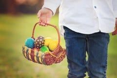 Śliczna urocza chłopiec, zbiera Easter jajka w wiośnie kwitnie ch Zdjęcie Stock