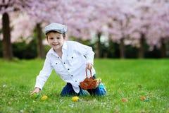 Śliczna urocza chłopiec, zbiera Easter jajka w wiośnie kwitnie ch Zdjęcia Stock