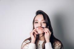 Śliczna urocza młoda kobieta robi wąsowi z jej włosy zdjęcie stock