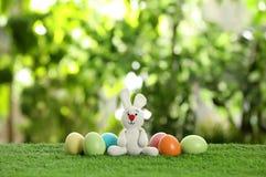 Śliczna Wielkanocnego królika zabawka i farbujący jajka na zielonej trawie obraz royalty free
