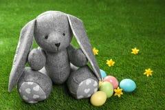 Śliczna Wielkanocnego królika zabawka i farbujący jajka na zielonej trawie fotografia royalty free