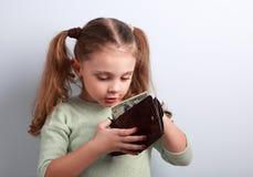 Śliczna zaskakująca mała dzieciak dziewczyna patrzeje w macierzystym portflu i chce obraz royalty free