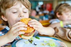 Śliczna zdrowa preschool dzieciaka chłopiec je hamburgeru obsiadanie w szkoły lub pepiniery kawiarni Szczęśliwy dziecko je zdrowy obraz royalty free