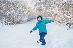 Śliczne chłopiec sztuki w zima lesie Zdjęcia Royalty Free