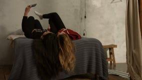Śliczne dziewczyny kłama na łóżku bierze selfie do góry nogami zbiory wideo