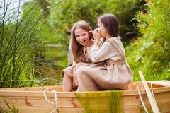 Śliczne małe dziewczynki ma zabawę w łodzi rzeką Obraz Stock
