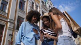 Śliczne multiracial dziewczyny dzieli mądrze telefon outdoors zbiory