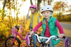 Śliczne siostry jedzie rowery w miasto parku na pogodnym jesień dniu Aktywny rodzinny czas wolny z dzieciakami Dzieci jest ubrany fotografia stock