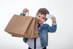 Śliczne uśmiechnięte dziecka mienia rabata bielu karty ręki i torby na zakupy w jego Dzieciak z kartą kredytową fotografia royalty free