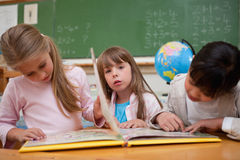 Śliczne uczennicy czyta bajkę ich kolega z klasy Obrazy Stock