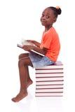 Ślicznego czarnego afrykanina amerykańska mała dziewczynka czyta książkę - afrykanin Zdjęcie Stock