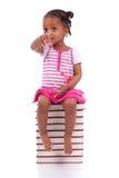 Ślicznego czarnego afrykanina amerykańska mała dziewczynka sadzająca w stercie okrzyki niezadowolenia Obrazy Royalty Free