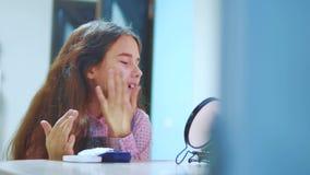 Ślicznej brunetki małej dziewczynki kładzenia Latynoska śmietanka na jej twarzy Śmieszna młoda dziewczyna z maską dla skóry twarz zbiory wideo