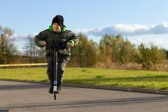 Ślicznej chłopiec jeździecka hulajnoga, plenerowa w jesieni środowisku na zmierzchu ciepłym świetle zdjęcie stock