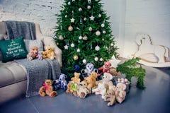 Ślicznej chłopiec siedzący puszek dekorującą choinką z zabawkami, misiami i prezentów pudełkami, obrazy royalty free