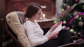Ślicznej dziewczyny czytelnicza książka blisko choinki zbiory