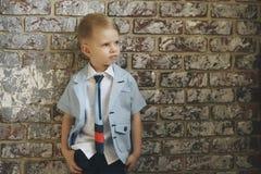 Ślicznej eleganckiej chłopiec pobliski lekki ściana z cegieł zdjęcie stock