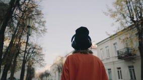 Ślicznej młodej dziewczyny chodząca ulica między budynkami i słuchającą muzyką w hełmofonach, miastowy styl, elegancki modniś nas zbiory