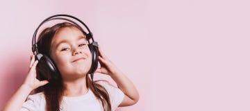 Ślicznej małej dziewczynki słuchająca muzyka jest ubranym słuchawki zdjęcia stock