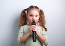 Ślicznej zabawa dzieciaka dziewczyny śpiewacka piosenka w mikrofonie na błękitnym tle Fotografia Royalty Free
