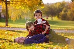 Śliczni śmieszni dzieci, bawić się z ich ojcem w parku, aut obrazy stock
