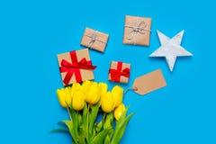 Śliczni żółci tulipany, piękni prezenty i gwiazda, kształtowali zabawkę na w Zdjęcie Stock