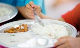Śliczni azjatykci dzieciak chłopiec łasowania foods jaźnią Dziecko trzyma łyżkę zdjęcia stock