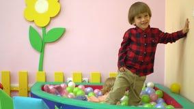 Śliczni caucasian preschool berbecie bawić się w wielo- coloured balowym basenie Przedszkole zdjęcie wideo