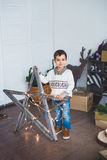 Śliczni chłopiec stojaki blisko drewnianej gwiazdy w studiu Obraz Stock