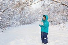 Śliczni chłopiec stojaki i utrzymanie śnieg w parku Fotografia Royalty Free