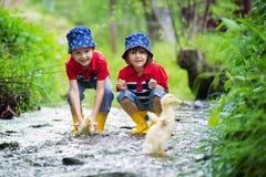 Śliczni dzieci, chłopiec bracia, bawić się z łodzią i kaczkami na li Zdjęcia Royalty Free