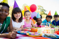Śliczni dzieci ono uśmiecha się i pozuje podczas przyjęcia urodzinowego Zdjęcia Stock