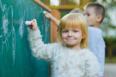 Śliczni dzieci rysuje z kredą na blackboard plenerowym Fotografia Stock