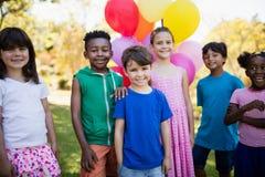 Śliczni dzieci stoi i pozuje podczas przyjęcia urodzinowego Obrazy Royalty Free