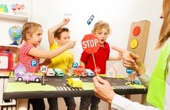 Śliczni dzieciaki ma zabawy nauczania ruchu drogowego znaki obrazy stock