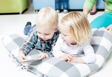 Śliczni dzieciaki przeglądają książkę obrazy royalty free