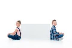 Śliczni dzieciaki siedzi z pustym sztandarem i ono uśmiecha się przy kamerą Fotografia Royalty Free