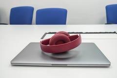 Śliczni foldable bezprzewodowi hełmofony dla kobiety i laptopu w miejsce pracy zdjęcia stock