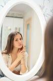 Śliczni młodych dziewczyn spojrzenia przy ona w lustrze Zdjęcie Stock