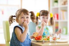 Śliczni małe dzieci je jedzenie przy daycare Obraz Royalty Free