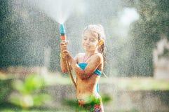 Śliczni małych dziewczynek sprinkls woda dla ona od węża elastycznego, mak obraz stock